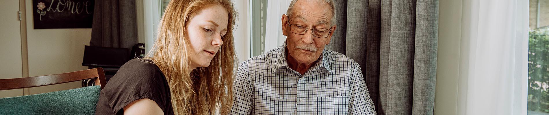 Oude man krijgt hulp bij de dagverzorging van Liante